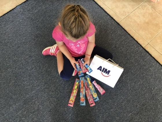 """Μετά το τέλος της ενημέρωσης έδωσαν σε κάθε παιδί προϊόντα στοματικής υγιεινής, προσφορά της Εταιρίας AIM και της αλυσίδας Supermarkets """"ΜΑΣΟΥΤΗΣ""""."""